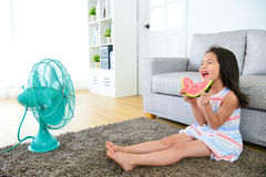 Little girl children sitting on living room floor. Happy little girl children sitting on living room floor blowing electric fan cool wind and eating fresh Royalty Free Stock Photography