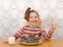 Little girl with chocolate donuts and thumb up Royalty Free Stock Image