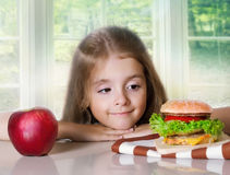 Little girl choose between apple and hamburger.Unhealthy nutriti Royalty Free Stock Image