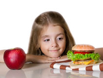 Little girl choose between apple and hamburger.Unhealthy nutriti Royalty Free Stock Photos