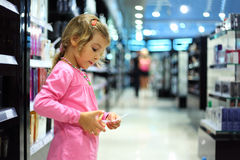 Little girl choose perfume in perfume shop Stock Photos