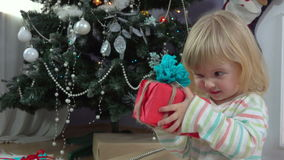 Little girl chooses a gift near the Christmas tree