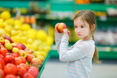 Little girl choosing an apple in a food store Royalty Free Stock Images
