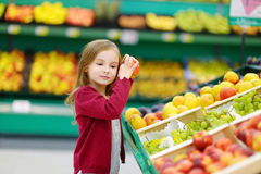 Little girl choosing an apple in a store Royalty Free Stock Images