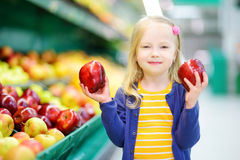 Little girl choosing apples in a food store or a supermarket Stock Image