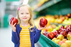 Little girl choosing apples in a food store or a supermarket Royalty Free Stock Image