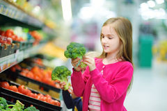 Little girl choosing broccoli in a food store or a supermarket Stock Photography