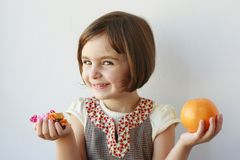 Little girl choosing candies or fruits Royalty Free Stock Images