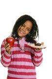 Little girl choosing between cupake and apple stock photo