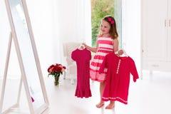 Little girl choosing dresses in white bedroom Royalty Free Stock Image