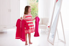 Little girl choosing dresses in white bedroom Royalty Free Stock Photos