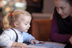 Little girl choosing foood from menu Stock Images