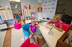 Little girl choosing glasses Stock Image