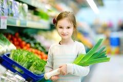Little girl choosing a leek in a food store Stock Photo