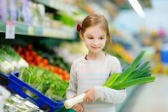 Little girl choosing a leek in a food store Royalty Free Stock Photo