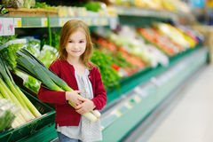 Little girl choosing a leek in a store Royalty Free Stock Photos