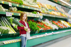 Little girl choosing a leek in a store Royalty Free Stock Images