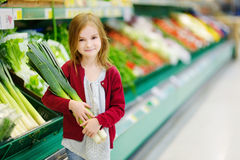 Little girl choosing a leek in a store Royalty Free Stock Image