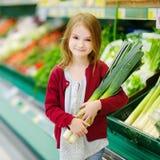 Little girl choosing a leek in a store Stock Photography
