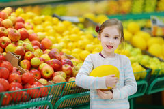 Little girl choosing a melon in a food store Royalty Free Stock Photo