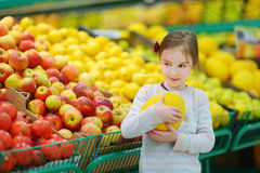 Little girl choosing a melon in a food store Royalty Free Stock Photos
