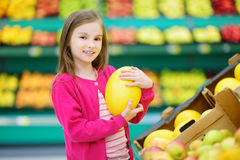 Little girl choosing a melon in a food store or a supermarket Stock Images