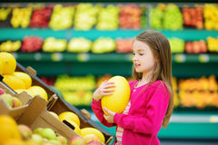 Little girl choosing a melon in a food store or a supermarket Stock Photos