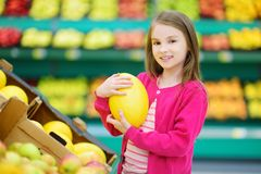 Little girl choosing a melon in a food store or a supermarket Royalty Free Stock Image