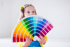 Little girl choosing paint color for wall. Family remodeling house. Home remodel and renovation. Kids painting walls with colorful brush and roller. Children stock image
