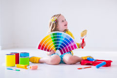 Little girl choosing paint color for wall. Family remodeling house. Home remodel and renovation. Kids painting walls with colorful brush and roller. Children royalty free stock photo