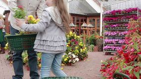 Little girl choosing plant and putting it in basket Royalty Free Stock Image