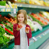 Little girl choosing tomatoes in a food store Royalty Free Stock Photos
