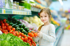 Little girl choosing tomatoes in a food store Stock Photography