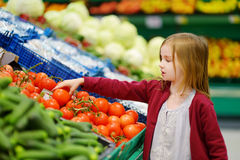 Little girl choosing tomatoes in a store Royalty Free Stock Photography