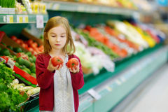 Little girl choosing tomatoes in a store Royalty Free Stock Images