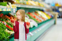 Little girl choosing tomatoes in a store Royalty Free Stock Photos