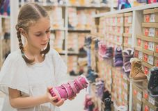Little girl choosing winter shoes. Stock Photo