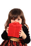 Little girl christmas. Cute three year old little girl dressed up in a fancy dress hiding behind a red giftbox on a white background Stock Image
