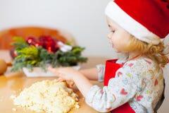Christmas baking. Little girl at christmas bakery stock photo