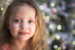Little girl at Christmas with Christmas tree at background royalty free stock photos