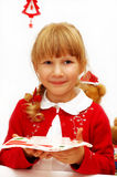 Little girl with christmas eve wafer on plate Stock Image