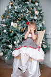 Little Girl with Christmas gift. close her eyes with her hands Royalty Free Stock Photography