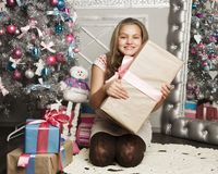 Little girl with Christmas gifts near a Christmas tree at home Royalty Free Stock Images