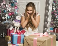 Little girl with Christmas gifts near a Christmas tree at home Stock Photos