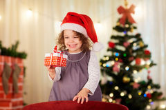 Little girl in Christmas hat of Santa Claus with a gift in hand. Is smiling in a room with decor Stock Photography