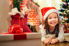 The little girl in Christmas hat of Santa Claus lying on the flo. Or in the room with the decor, fireplace, smiling in the New Year Stock Images