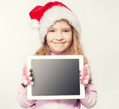Little girl in christmas hat with tablet Royalty Free Stock Image