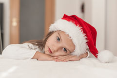 Little girl with Christmas hat waiting for Santa  at home in the Royalty Free Stock Photo
