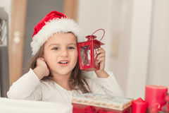 Little girl with Christmas hat waiting for Santa  at home in the Stock Photography