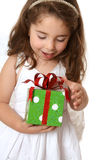 Little girl with a christmas or other present. A little girl with browin hair looks down in delight at a Christmas present Stock Photo